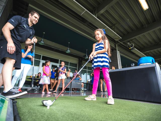 Child and instructor golfing